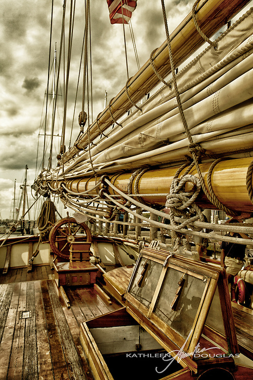 Mast,furled sails and rigging on the Pride of Baltimore II.  The Pride of Baltimore II is a reproduction of an 1812   Baltimore clipper privateer topsail schooner.  Also shown deck and ship's wheel.