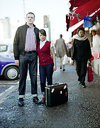 Couple Standing with Luggage, Dalston Market, London, UK, 1980s.