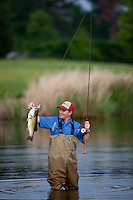 ANGLER WADING IN A FARM POND USING A BAITCASTING RIG AND ADMIRING HIS LARGEMOUTH BASS