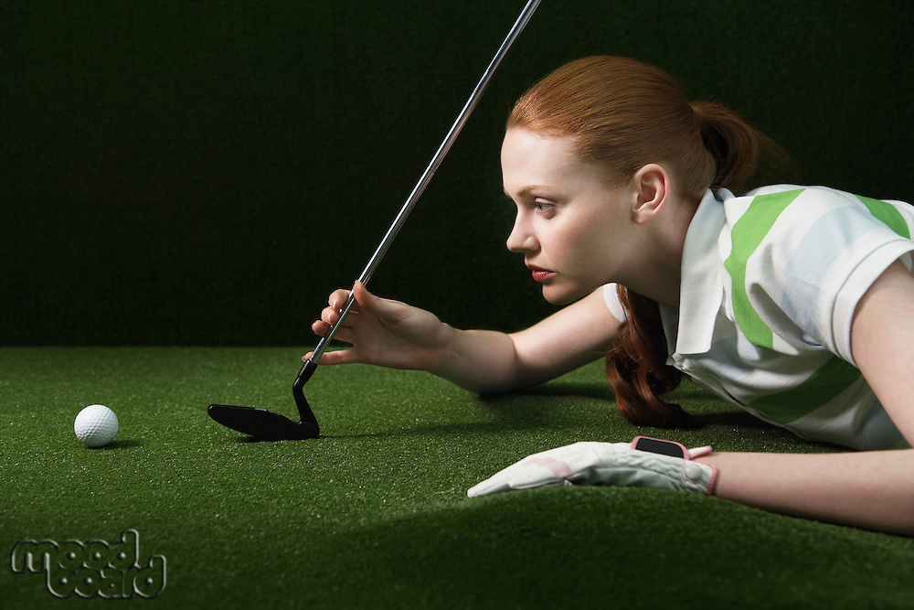 Woman reclining on floor holding golf club looking at golf ball