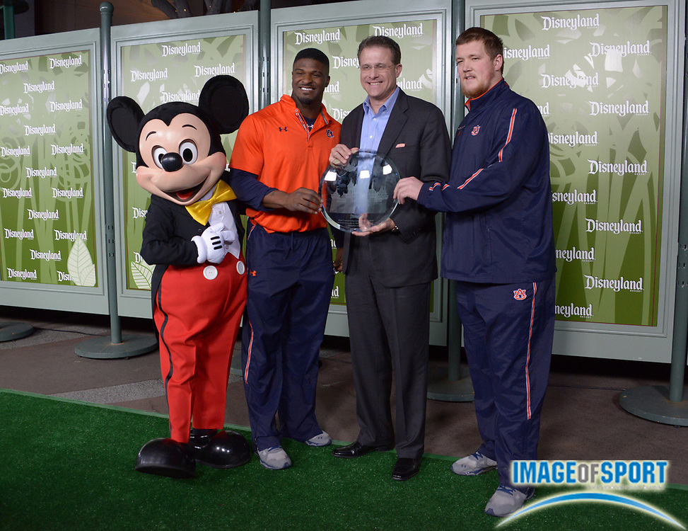 Dec 31, 2013; Anaheim, CA, USA; Auburn Tigers defensive end Dee Ford (second from left), coach Gene Malzahn (second from right) and center Reese Dismukes (right) pose with Mickey Mouse (left) at press conference for the 2014 BCS National Championship at ESPN Zone Downtown Disney.