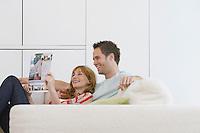 Couple reading brochure on sofa