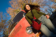 A young woman poses with her bag against an old VW bus