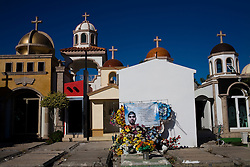 "Large chapels are built in the cemetary in Culiacan, Mexico, known locally as the ""Pantheon"".  Some of the chapels, where the dead are buried, are two-story buildings complete with electricity and air conditioning.  This phenomenon, where people build increasingly large, luxurious memorials to their dead family members, is often associated with Mexico's Narco Culture."