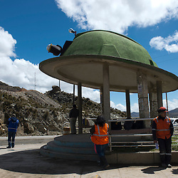 People wait for transportation at a helmet-shaped shelter at the entrance of the town of Morococha in the central Peruvian Andes. Chinese mining company Chinalco hopes to relocate the town to build the Toromocho Project.