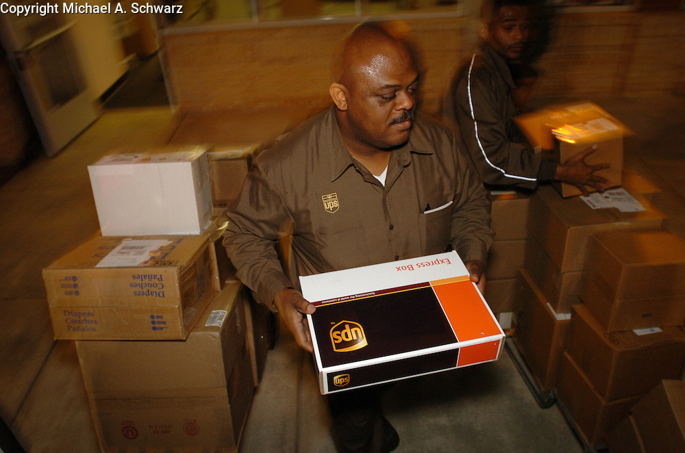December 16. 2003. Alpharetta, GA.  Scott McDuffee package being transported to Santa Rosa, CA<br /> <br /> UPS driver Ken Spencer picks up package at UPS store in Alpharetta, GA and loads it in truck with the help of Marcus Jenkins, who is a seasonal worker.