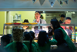 © Licensed to London News Pictures . 24/11/2015 . Oldham , UK .  Liberal Democrat leader TIM FARRON (c) and candidate JANE BROPHEY (l) working in the kitchen serving lunch whilst campaigning at St Thomas CofE Primary School in the seat of Oldham West and Royton , in a by-election triggered by the death of MP Michael Meacher . Photo credit : Joel Goodman/LNP