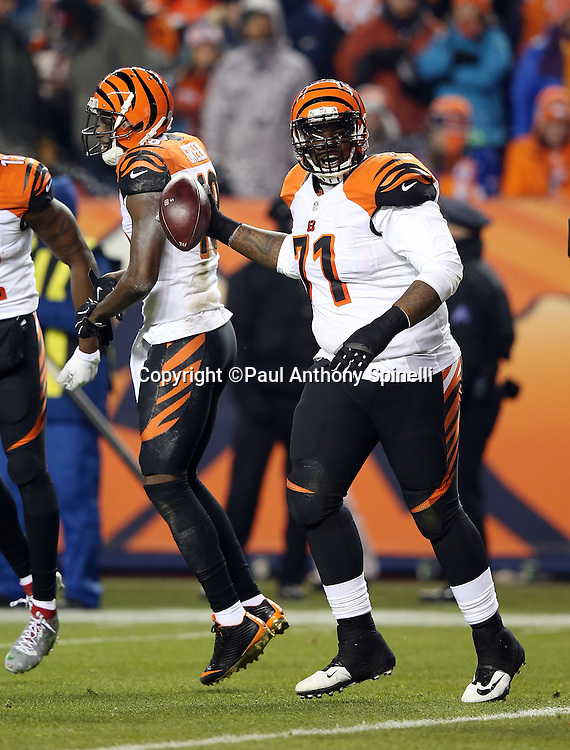 Cincinnati Bengals tackle Andre Smith (71) tosses the ball in celebration after Cincinnati Bengals wide receiver Mohamed Sanu (12) scores a second quarter touchdown good for a 14-0 Bengals lead during the 2015 NFL week 16 regular season football game against the Denver Broncos on Monday, Dec. 28, 2015 in Denver. The Broncos won the game in overtime 20-17. (©Paul Anthony Spinelli)