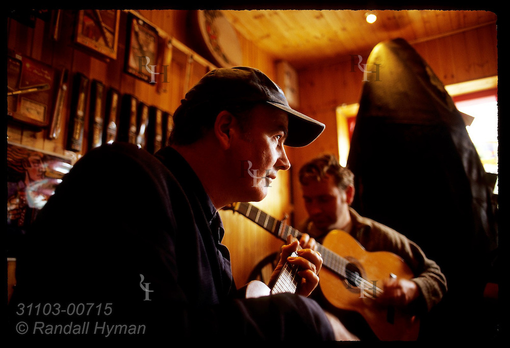 Two men play ukelele and guitar during a music store performance in town of Dingle, Ireland.