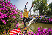 """09 DECEMBER 2013 - BANGKOK, THAILAND:  A Thai anti-government protestor runs across water main that spans a khlong (canal) in front of Government House in Bangkok. Thai Prime Minister Yingluck Shinawatra announced she would dissolve the lower house of the Parliament and call new elections in the face of ongoing anti-government protests in Bangkok. Hundreds of thousands of people flocked to Government House, the office of the Prime Minister, Monday to celebrate the collapse of the government after Yingluck made her announcement. Former Deputy Prime Minister Suthep Thaugsuban, the organizer of the protests, said the protests would continue until the """"Thaksin influence is uprooted from Thailand."""" There were no reports of violence in the protests Monday.     PHOTO BY JACK KURTZ"""