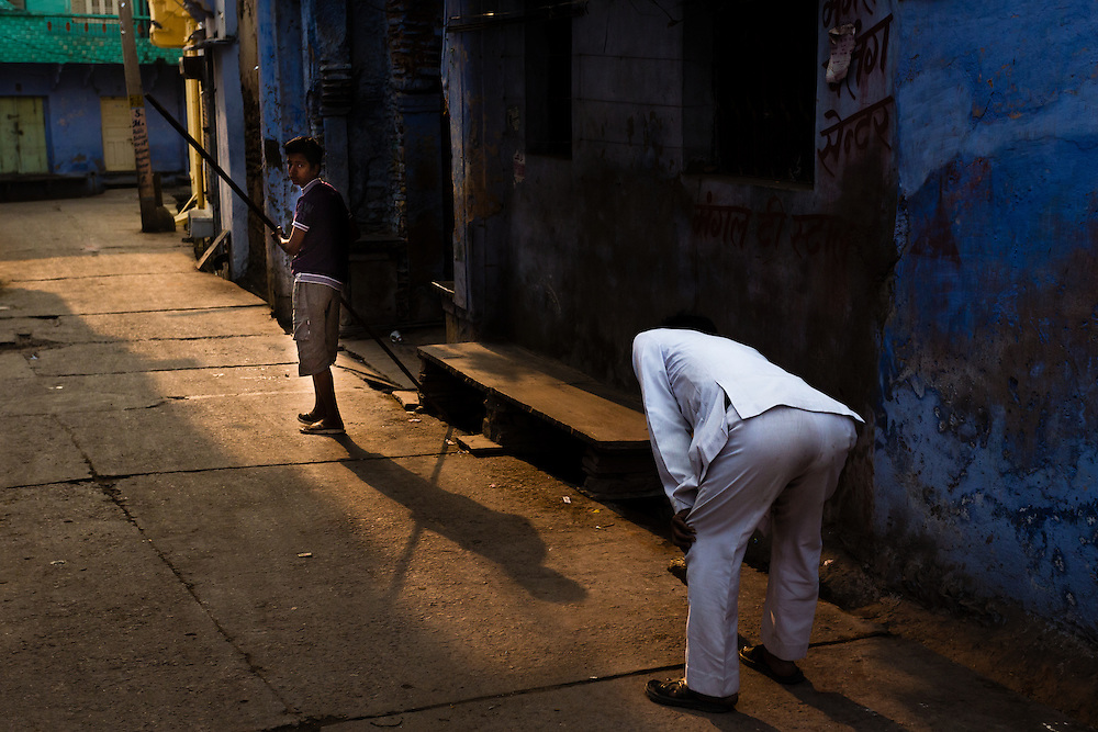 Early morning in Bundi, Rajasthan. A man dressed in white is sweeping the street in front of his home.