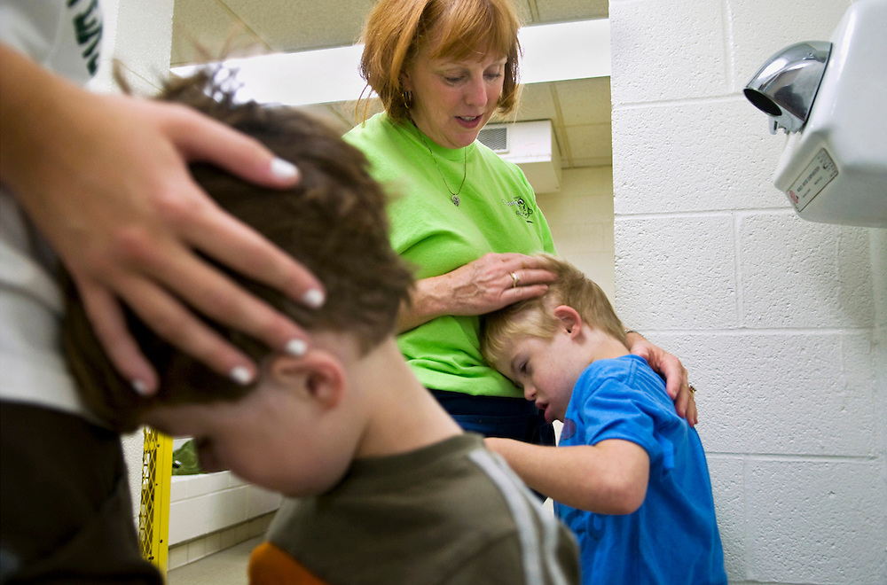 Lissa Riley dries the hair of Danny Caroll, 7, after a swim lesson.