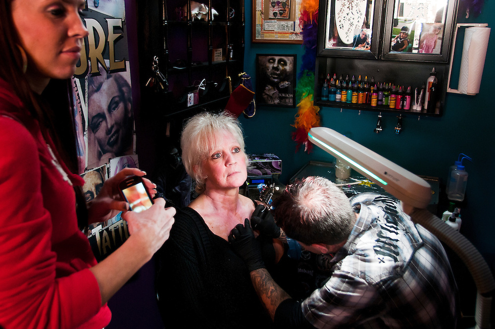 Heather Reed gets tattooed by Dave Pelletier at VooDoo Tattoo in Bay City, Mich., while her daughter Brandi Reed watches with a camera in hand on Sunday October 23, 2011. The two women participated in a 24-hour Tattoo-A-Thon to help raise money for the American Cancer Society.