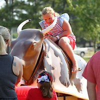 Allie Chidester, 7, of Tupelo, holds on tight as she rides a mechanical bull inflatible ride at Ballard Park for the Fourth of July Picnic in the Park Celebration Wednesday afternoon in Tupelo.