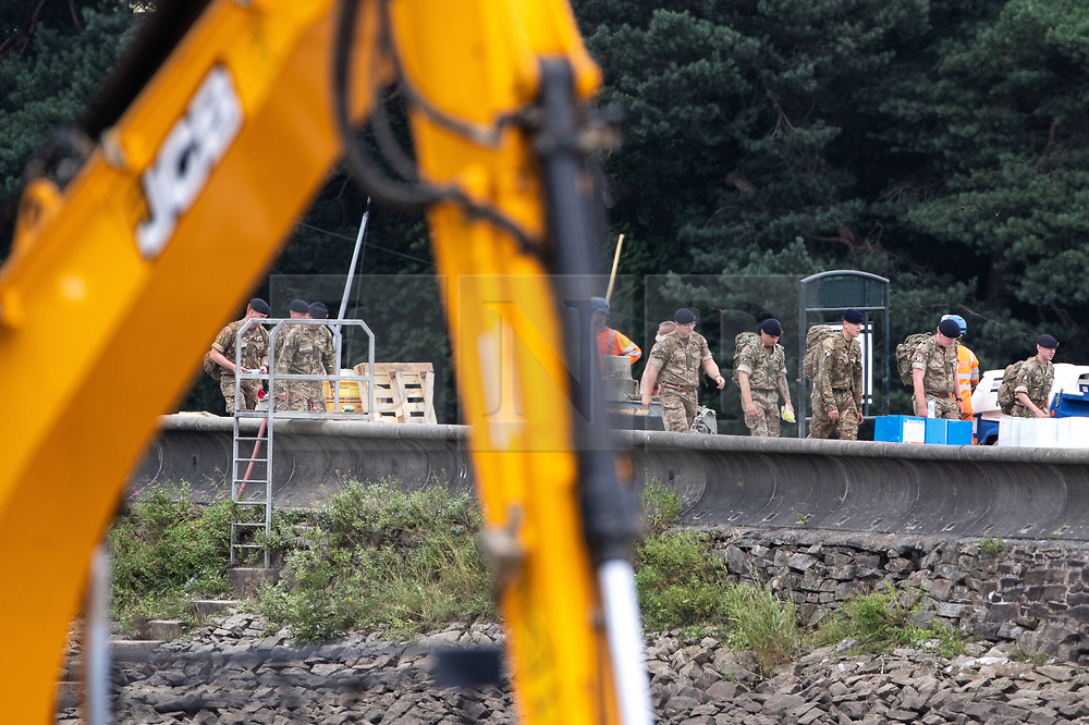 © Licensed to London News Pictures. 04/08/2019. Whaley Bridge, UK. Soldiers are seen crossing the reservoir . Watermarks on the rocks show the amount of water that has been pumped away since yesterday (Saturday 3rd August) . More rain is forecast today (Sunday 4th August) in the town of Whaley Bridge in Derbyshire after earlier heavy rain caused damage to the Toddbrook Reservoir , threatening homes and businesses with flooding. Photo credit: Joel Goodman/LNP
