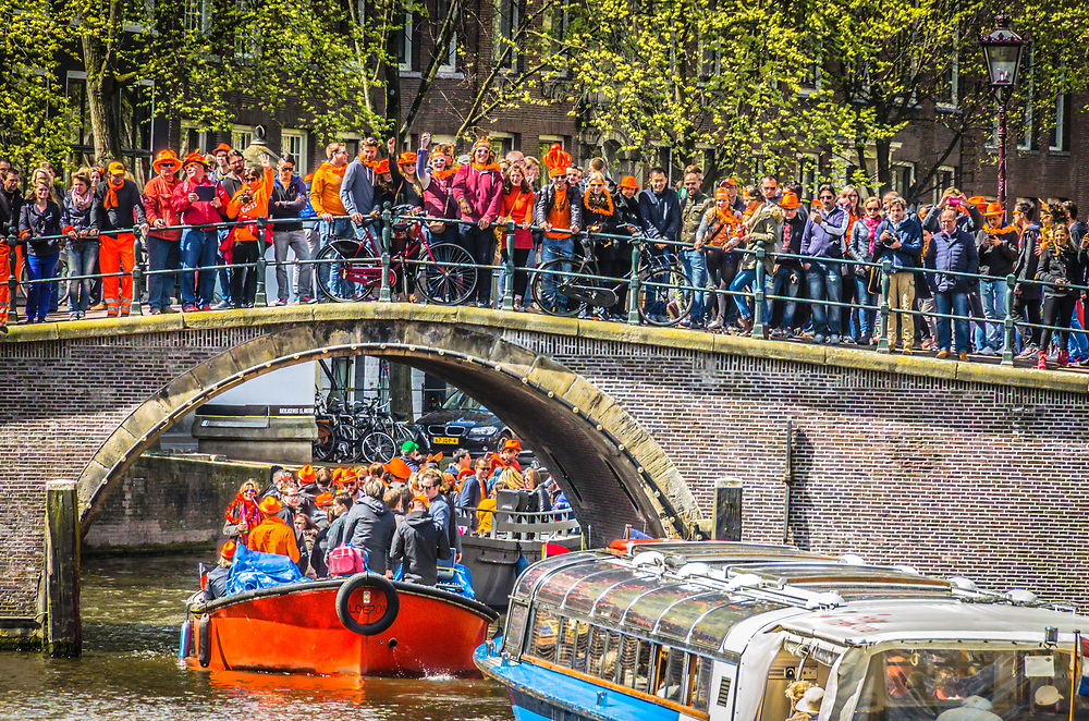 Crowds of people decked out in orange celebrate the Dutch holiday, King's Day, by  watching the boats on the Amsterdam Canals.