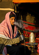 Young male Bedouin smoking a pipe at Captain's Desert Camp, Wadi Rum, Jordan