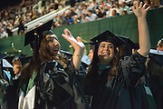 Friends Stephanie LaCavca (Left )and Ally Hays wave to family during graduate commencement. Photo by Ben Siegel