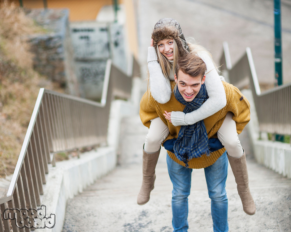 Portrait of smiling woman being piggybacked by man on stairway