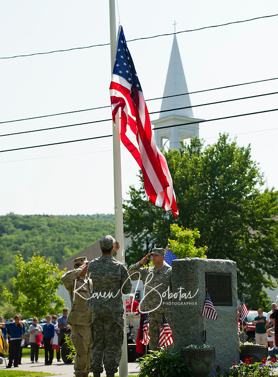Retired Lt. Col. Kurt Webber and Major Wayne Boutwell salute as Cadet Ken Webber raises the American flag at the World War I & II Memorial at the start of Gilford's Memorial Day parade on Monday morning.  (Karen Bobotas/for the Laconia Daily Sun)