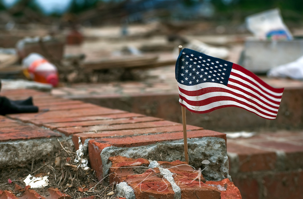 An American flag waves amid the rubble of a demolished home May 15, 2011 in Smithville, Mississippi. Jesse Cox, 85, died in the house, and his wife, Nell Cox, 75, was seriously injured when an EF5 tornado swept through the town on April 27, 2011. (Photo by Carmen K. Sisson/Cloudybright)