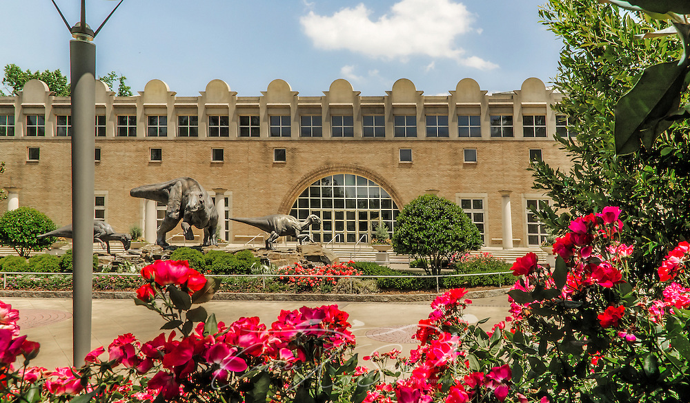 "Flowers bloom in front of the Fernbank Museum of Natural History, in Atlanta, Georgia, May 23, 2014. Dinosaur Plaza, located in front of the building, features a family of dinosaurs — lophorhothon atopus — frolicking in the fountain. The museum opened in 1992 and is known for its massive dinosaur exhibitions. The museum also has an IMAX theater and holds popular public events like monthly salsa dance nights and the weekly ""Martinis & IMAX"" program. (Photo by Carmen K. Sisson/Cloudybright)"