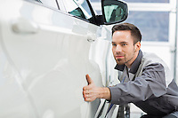 Young maintenance engineer examining car in repair shop