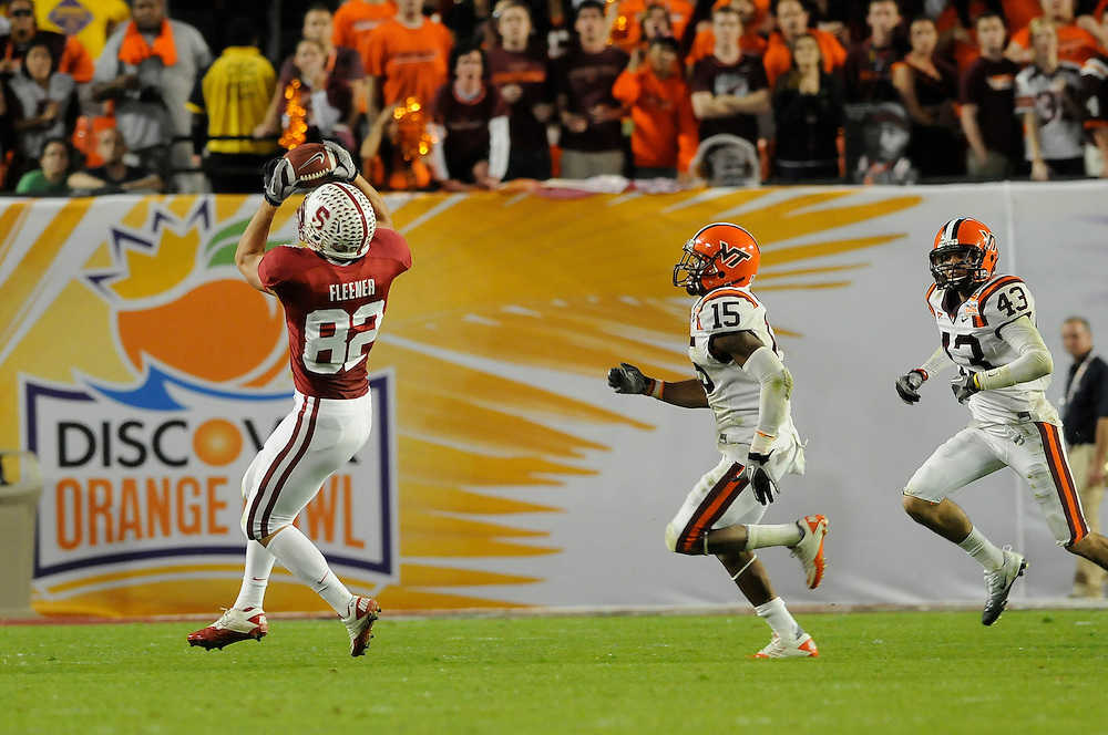 January 3, 2011: Coby Fleener of the Stanford Cardinal catches a pass as Eddie Whitley and Jeron Gouveia-Winslow of the Virginia Tech Hokies persue during the NCAA football game between the Stanford Cardinal and the Virginia Tech Hokies at the 2011 Orange Bowl in Miami Gardens, Florida. Stanford defeated Virginia Tech 40-12.