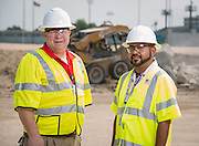 John Clark, left, and Magdaleno Orozco, right, pose for a photograph at the Delmar-Tusa Fieldhouse construction site, July 24, 2014.