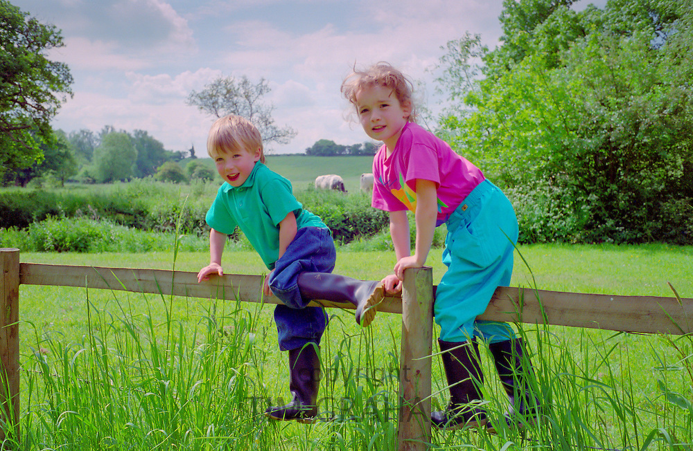A four year old boy and six year old girl climbing a wooden fence in Wiltshire, England