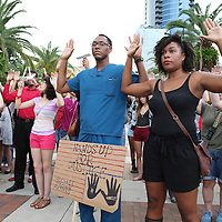 "People raise their arms in Lake Eola park during the ""National Moment of Silence"" event at the Lake Eola bandshell in downtown Orlando, Florida on Thursday, August 14, 2014. In light of the recent killing of eighteen year old Mike Brown in Ferguson, Missouri, citizens across America are gathering in solidarity to hold vigils and observe a moment of silence to honor victims of suspected police brutality. (AP Photo/Alex Menendez)"