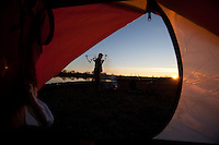 bowhunter standing outside of his tent at sunset