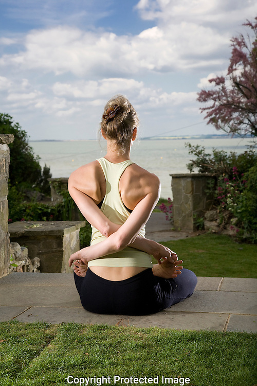 yoga teacher holding position on top step in garden with view of sea