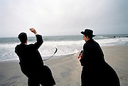 Two young Jewish men pray as strong hurricane winds hit the beach at Coney Island, Brooklyn.