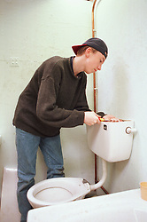 Young man learning plumbing skills mending toilet,