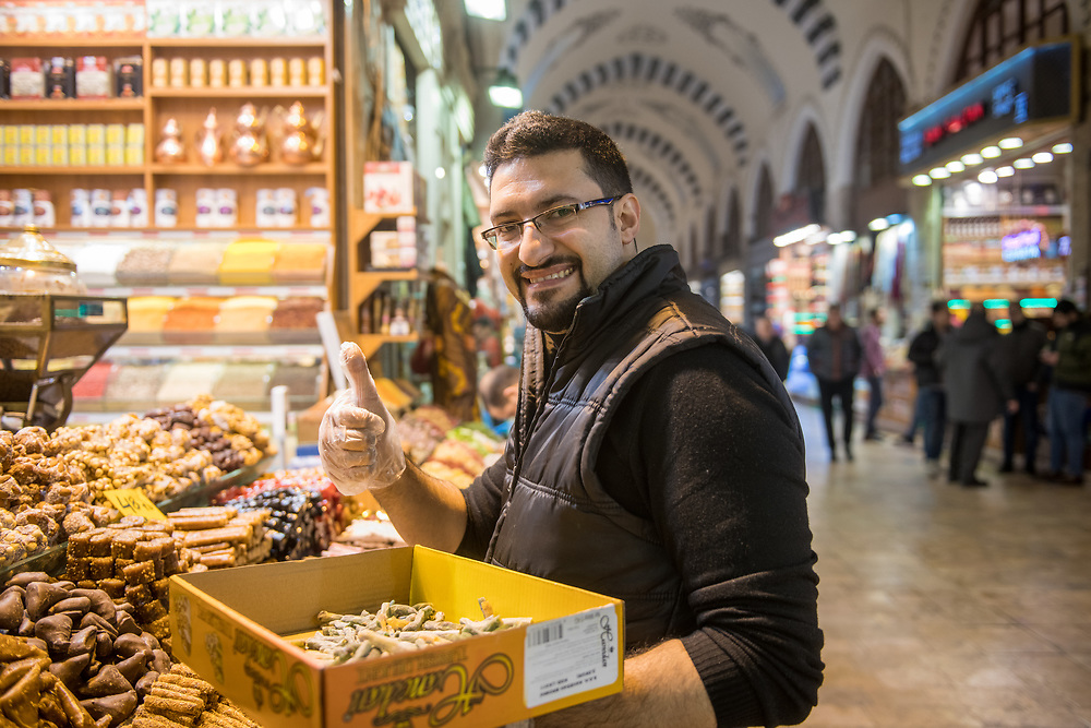 Adult male gives a thumbs up as he restocks bins in front of spice shop at Istanbul Spice bazaar in Turkey