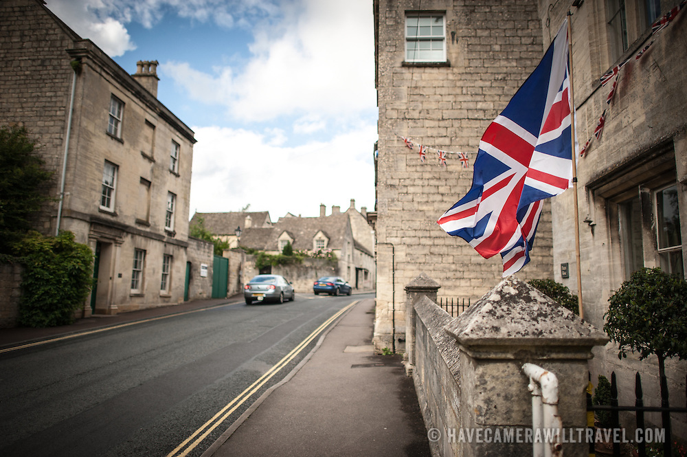 A Union Jack flies in the breeze at the entrance to a residential home in Painswick, Gloucestershire, with cars passing by.