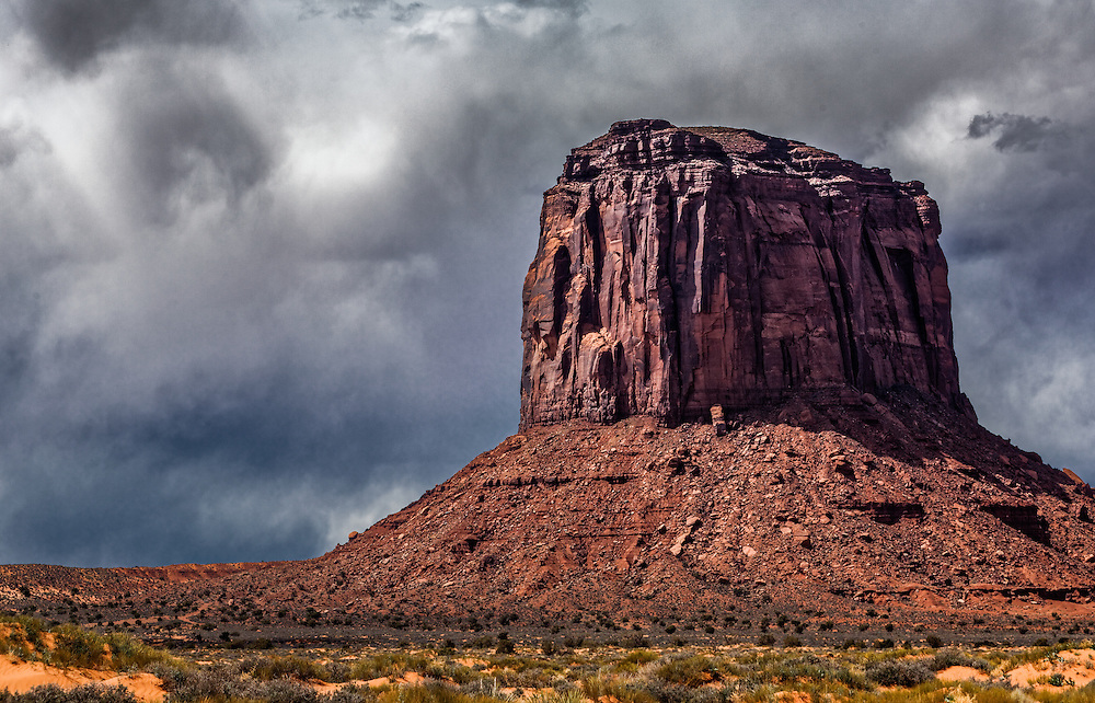 The sun lights one side of this Monolith in Monument Valley just before a storm rolls in.