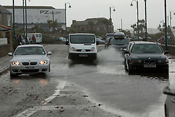 © Licensed to London News Pictures. 15/08/2012. Penzance, UK. Two cars drive through a flood caused by sea water deposited on the road by strong winds and large waves along Penzance Promenade. The Police closed the road due to the waves crashing over the road due to high winds but many motorist ignored the warnings. Photo credit : Ashley Hugo/LNP