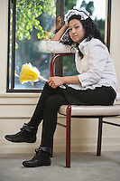 Pensive housemaid sitting on chair with a feather duster