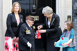 © Licensed to London News Pictures. 25/010/2018. London, UK. Prime Minister Theresa May places money in a charity box as she meets fundraisers Claire Rowcliffe, Director of Fundraising at The Royal British Legion, Barbara Windsor (93) and Poppy Railton (9) for the Royal British Legion and purchase a poppy to launch the National Poppy Appeal 2018 outside 10 Downing Street. Photo credit: Dinendra Haria/LNP