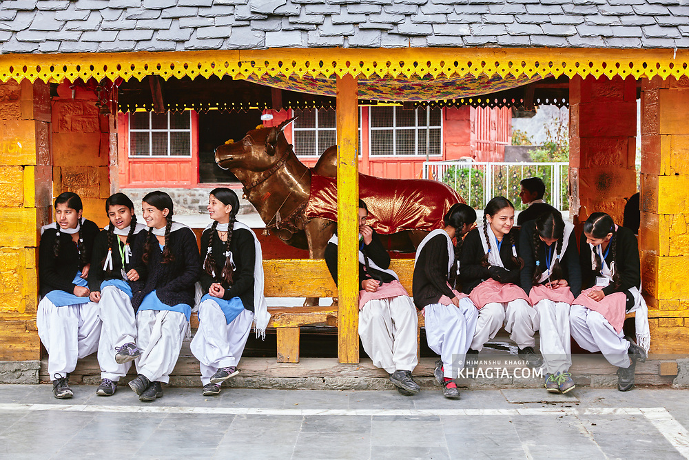 School girls resting under an old wooden structure in Chaurasi temple complex in Bharmaur, Chamba, Himachal Pradesh, India