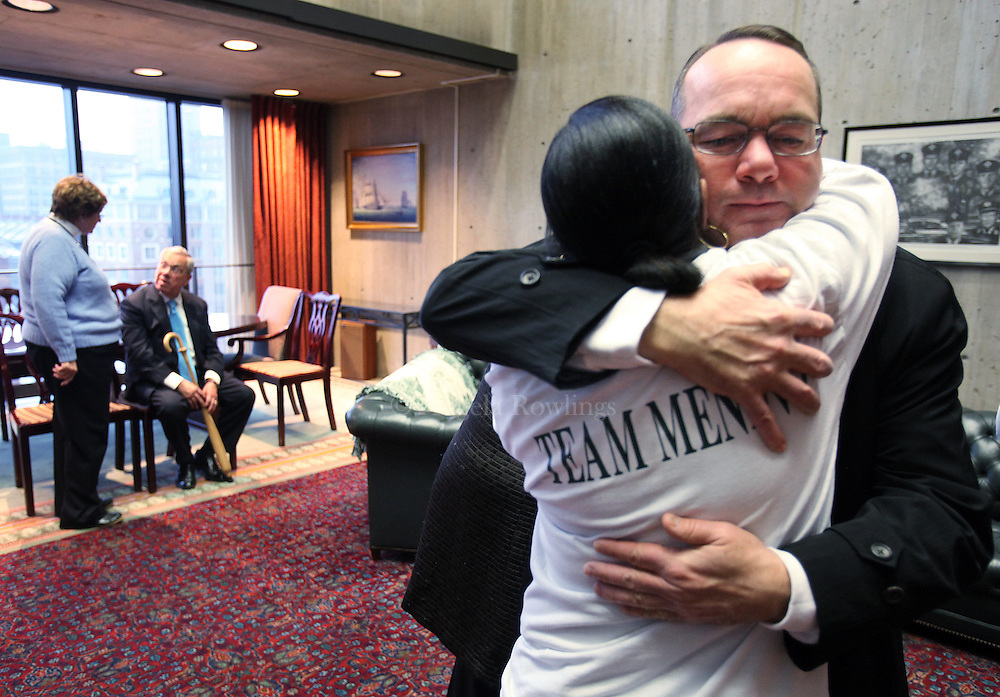(Boston, MA - 1/6/14) Mayor Thomas Menino, background, speaks with a staffer as Michael Kineavy, chief of policy and planning, right, hugs Menino's administrative assistant, Annette Gales, at Boston City Hall, Monday, January 06, 2014. Staff photo by Angela Rowlings.