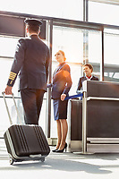 Portrait of young beautiful airport staff opening the gate for boarding while mature pilot walking in airport