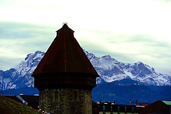 The Chapel Bridge (Kapellbrücke) with the Swiss Alps in the background.