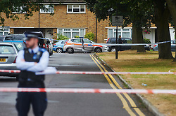 © Licensed to London News Pictures. 20/07/2015 Enfield, UK. A police officer stands at a cordon on Lackmore Road, Enfield after a man died following a stabbing. Police were called to the scene at 18:55hrs on Sunday, 19 July where a 28-year-old man had suffered a stab injury. He died at the scene at 19:31hrs. Three 18-year-old men have been arrested in connection with this incident. Photo credit : Simon Jacobs/LNP