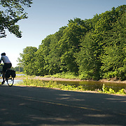 A woman cycles along a picturesque river along Katie Rd. The 2007 Trek Across Maine, an annual project of the American Lung Association of Maine (ALAM).