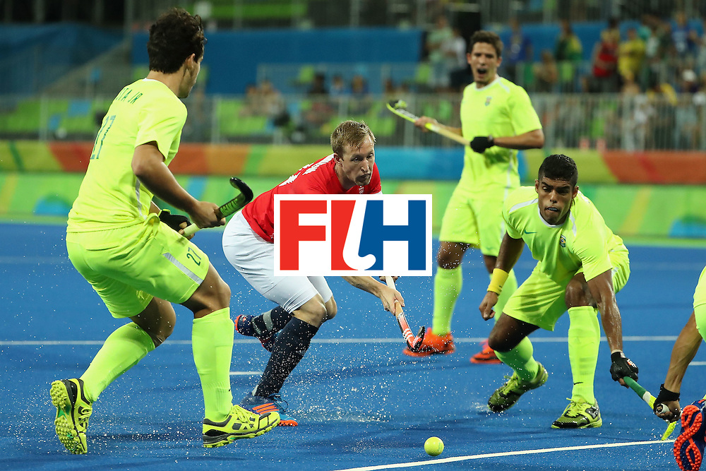 RIO DE JANEIRO, BRAZIL - AUGUST 09:  Barry Middleton #17 of Great Britain moves the ball past Paulo Batista #27 of Brazil during the hockey game on Day 4 of the Rio 2016 Olympic Games at the Olympic Hockey Centre on August 9, 2016 in Rio de Janeiro, Brazil.  (Photo by Christian Petersen/Getty Images)