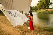 back to nature concept Woman in red dress hangs up washing on the riverbank