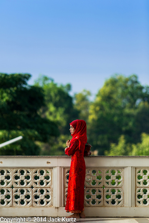 28 JULY 2014 - KHLONG HAE, SONGKHLA, THAILAND:  A woman waits for Eid services to start at Songkhla Central Mosque. Eid al-Fitr is also called Feast of Breaking the Fast, the Sugar Feast, Bayram (Bajram), the Sweet Festival and the Lesser Eid, is an important Muslim holiday that marks the end of Ramadan, the Islamic holy month of fasting.  PHOTO BY JACK KURTZ